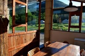 L'espace cuisine et ses baies vitrées donnant sur les yourtes et la montagne